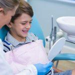 Dentist showing mirrior to boy