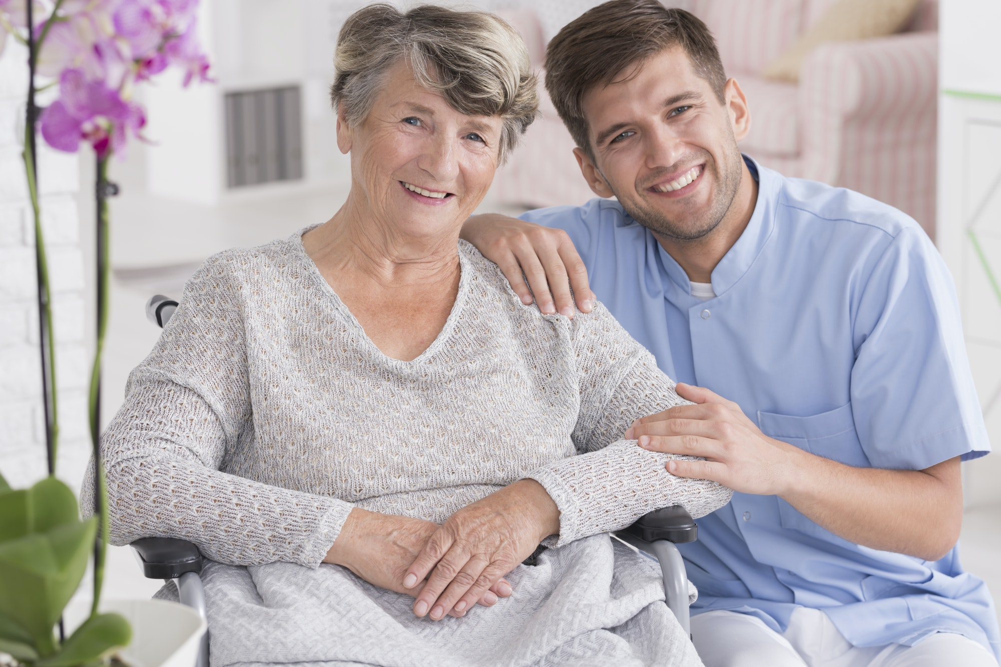 Smiling carer with senior in rest home