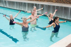 Trainer with senior people exercising in swimming pool